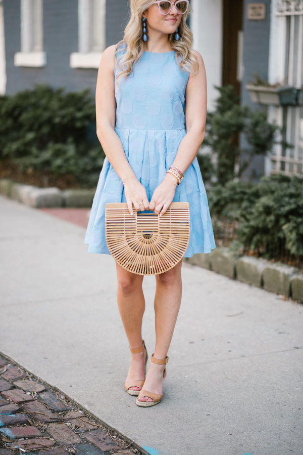 Jessica of Bows & Sequins wearing a Sail to Sable fit and flare dress with a Cult Gaia bamboo bag with Vince Camuto ankle strap wedge sandals.