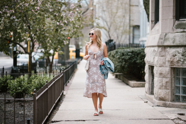 Travel blogger Bows & Sequins wearing an ASTR tie-front floral midi dress for a music festival.