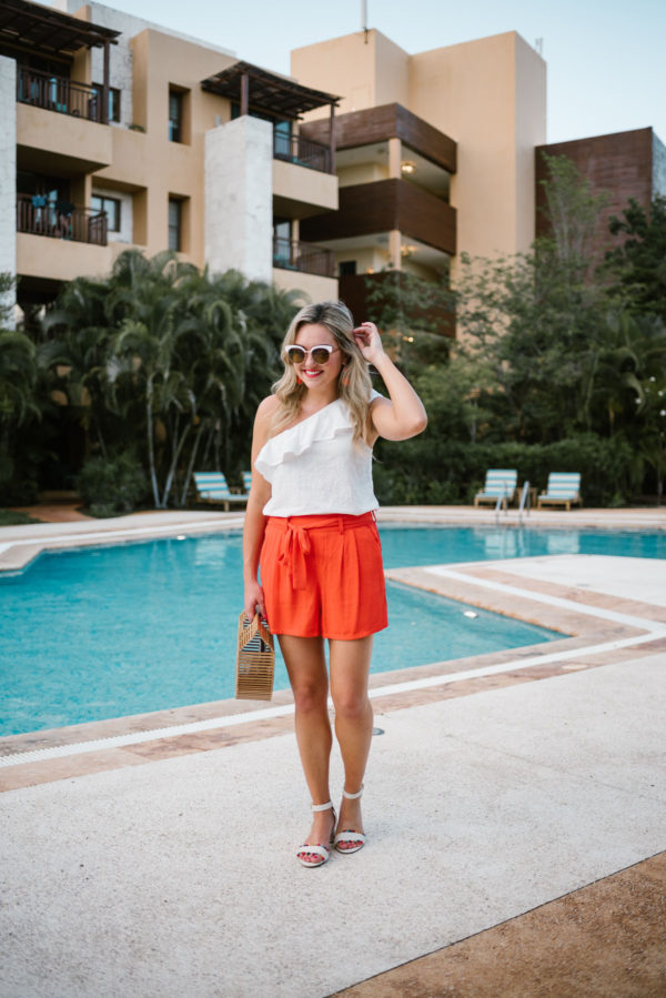 Bows & Sequins wearing a single shoulder ruffle top from Old Navy, orange tie-waist shorts, and J.Crew pom pom sandals.