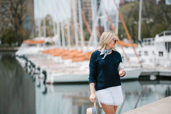 Fashion blogger Bows & Sequins wearing a blue bandana neckerchief with an Old Navy summer sweater and white eyelet shorts.