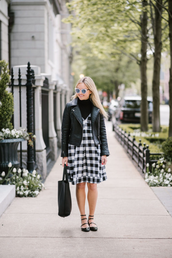 Bows & Sequins wearing a black gingham midi dress with a moto jacket, a leather tote, and strappy Mary Janes.