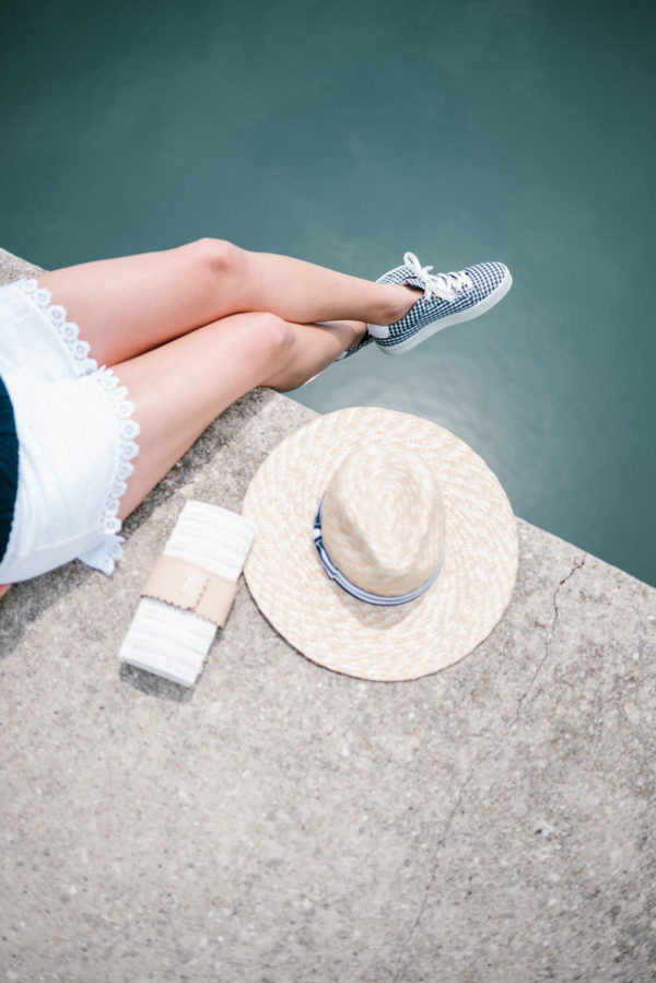 Lifestyle blogger Bows & Sequins wearing Kensie eyelet shorts and gingham sneakers with a Vineyard Vines wicker clutch and a straw hat.