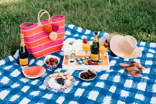 Chicago fashion blogger Bows & Sequins hosts a summer picnic on Lake Michigan with a blue gingham picnic blanket, a striped Mar y Sol straw tote and orange champagne flutes.