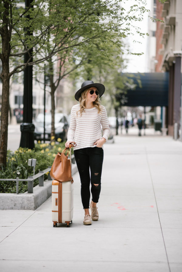 Fashion blogger Bows & Sequins wearing a Kenzie sweater with Old Navy black jeans, a straw hat, and espadrille sneakers.