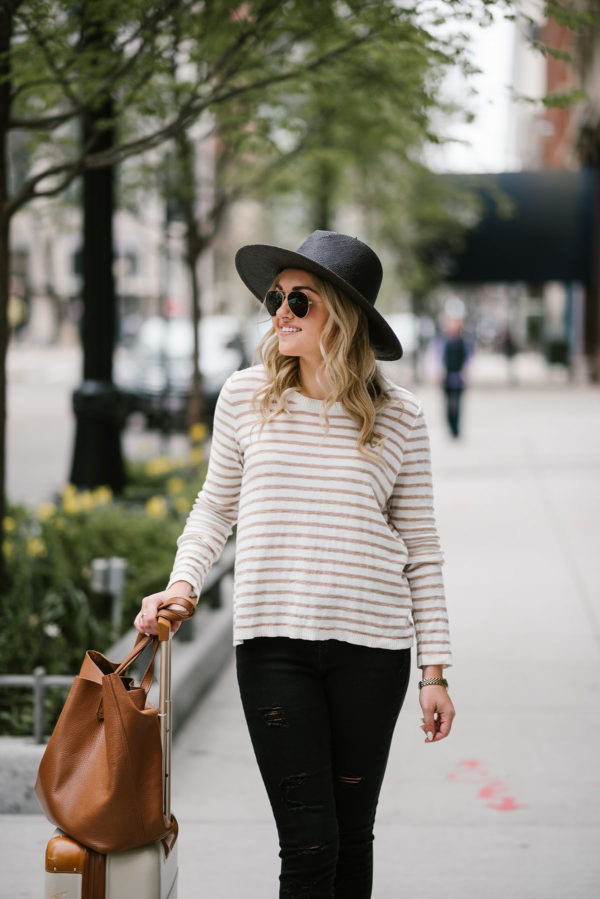 Chicago blogger Bows & Sequins wearing a black straw Janessa Leone hat with gold Ray-Ban aviators, a striped Kenzie sweater, and Old Navy jeans with a Cuyana leather tote for travel.