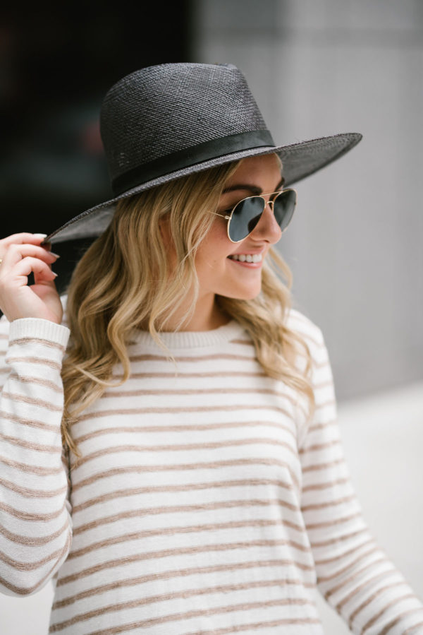 Jessica of Bows & Sequins styling a black Janessa Leone hat with a striped Kenzie sweater and gold Ray-Ban aviators.