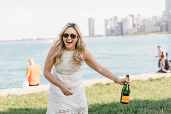 Fashion blogger Bows & Sequins holding a bottle of Veuve Clicquot champagne.