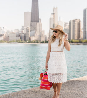 Fashion blogger Bows & Sequins wearing a white lace J.O.A. dress, an Old Navy straw hat, and holding a striped Mar y Sol tote.
