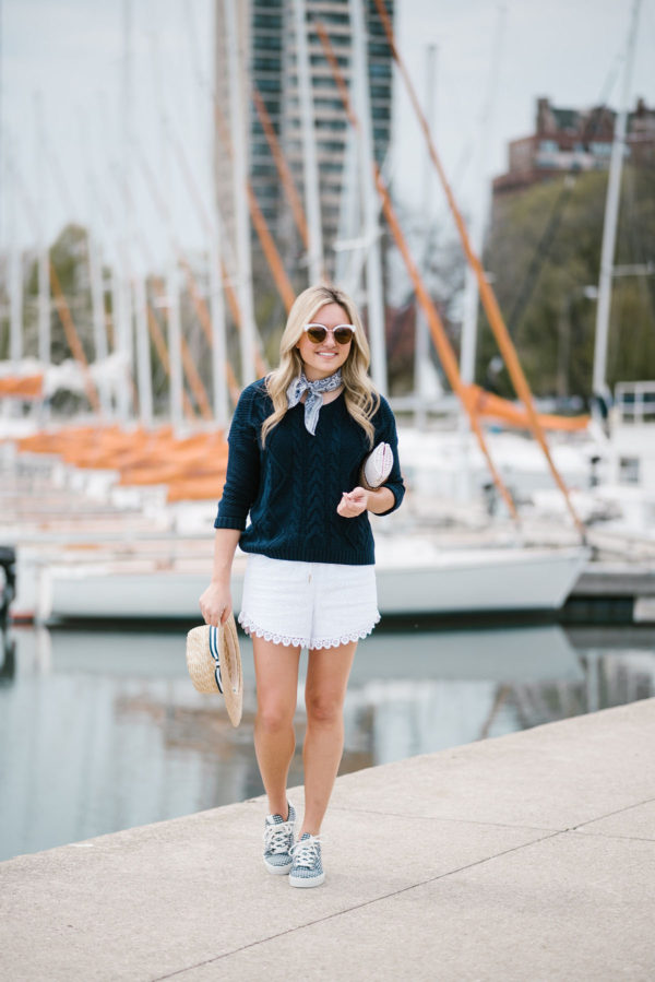 Bows & Sequins wearing a navy summer sweater and white eyelet shorts with gingham shoes and a straw hat.