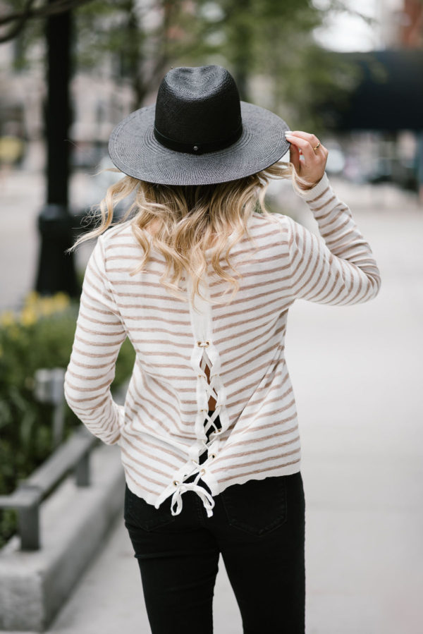 Bows & Sequins wearing a Kenzie tie-back sweater with a black straw hat and Old Navy jeans.