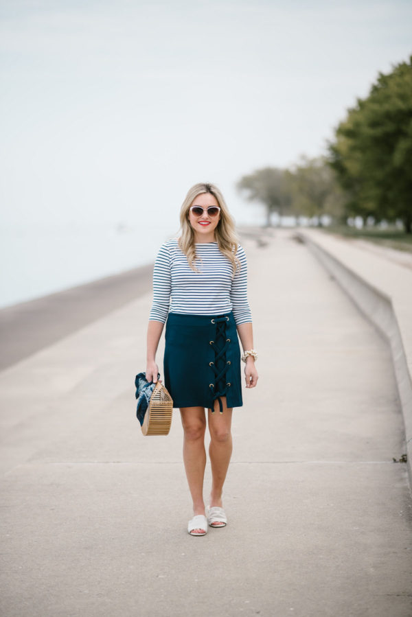 Chicago lifestyle blogger Bows & Sequins wearing Call It Spring sunglasses, a Lands End navy striped tee, a lace-up skirt, and a bamboo handbag.