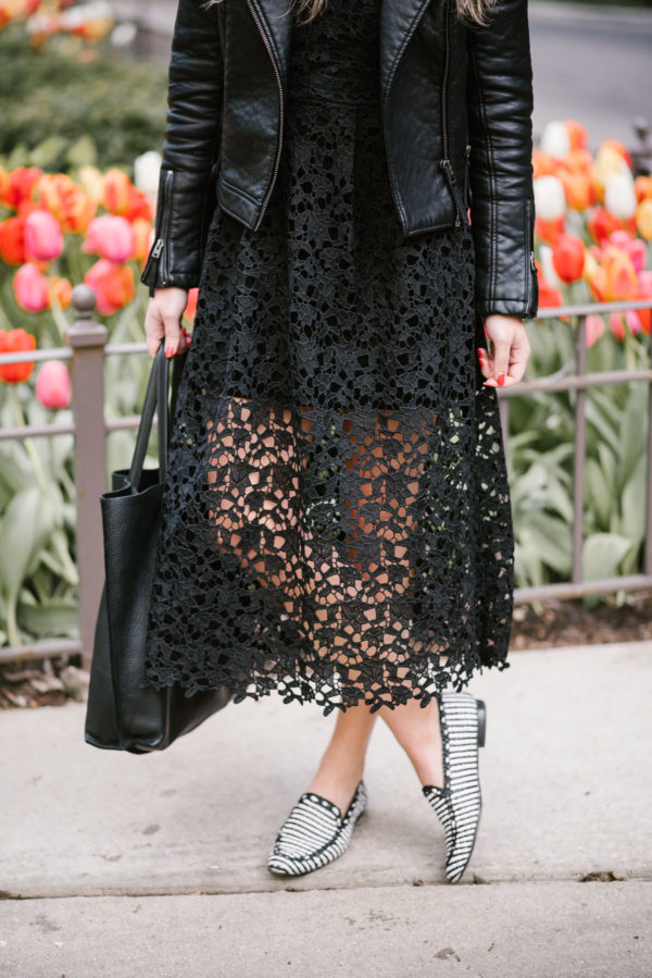 Chicago blogger Bows & Sequins wearing a black ASTR lace dress from Nordstrom, a black Topshop moto jacket, and KSNY loafers with a leather tote.