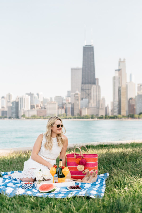 Chicago blogger Bows & Sequins wearing a J.O.A. lace dress with a Mar y Sol straw tote on a Crate & Barrel blue gingham blanket.