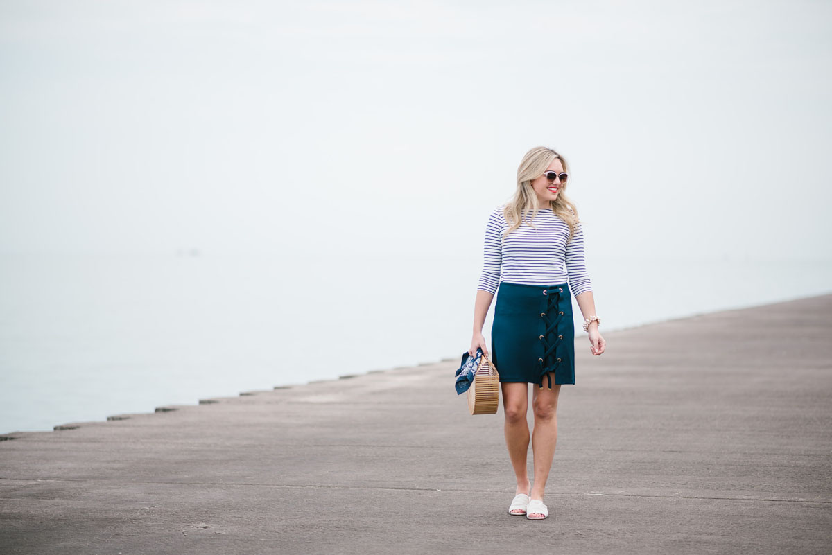 Fashion and style blogger Jessica Sturdy of Bows & Sequins wearing a three quarter sleeve tee and navy skirt with white slides and a bamboo bag.