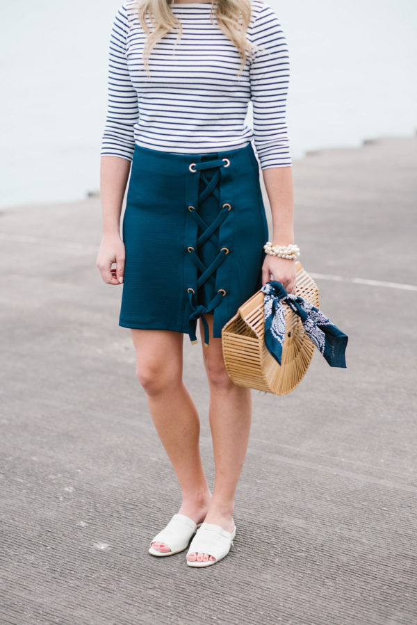 Chicago lifestyle blogger Bows & Sequins wearing a Lands End striped tee and a navy skirt with a Cult Gaia bamboo bag, a navy bandana, and a Sweet & Spark pearl bracelet.