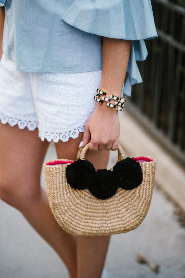 Chicago fashion blogger Bows & Sequins styling a JadeTribe pom pom bag with a Lele Sadoughi bracelet and Kensie eyelet shorts.