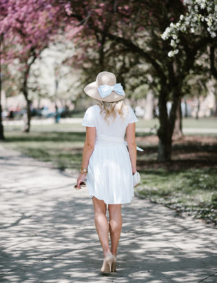 Bows & Sequins wearing a little white dress with a bow hat in Chicago.