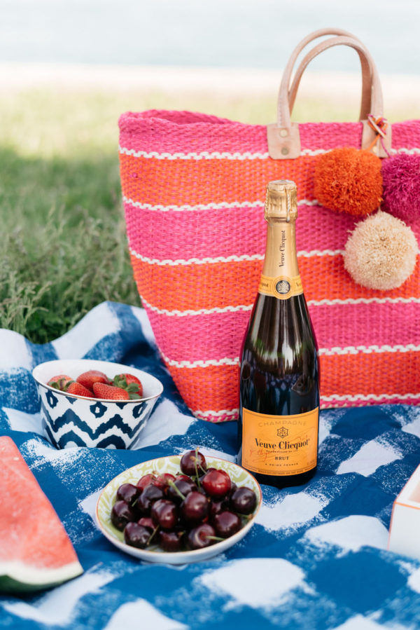 Veuve Clicquot champagne bottle and pink striped Mar y Sol tote on a Crate & Barrel blue gingham blanket.