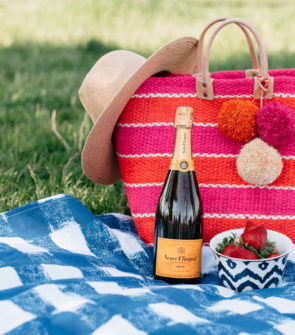 An Old Navy straw hat with a Mar y Sol striped tote on a blue gingham picnic blanket.