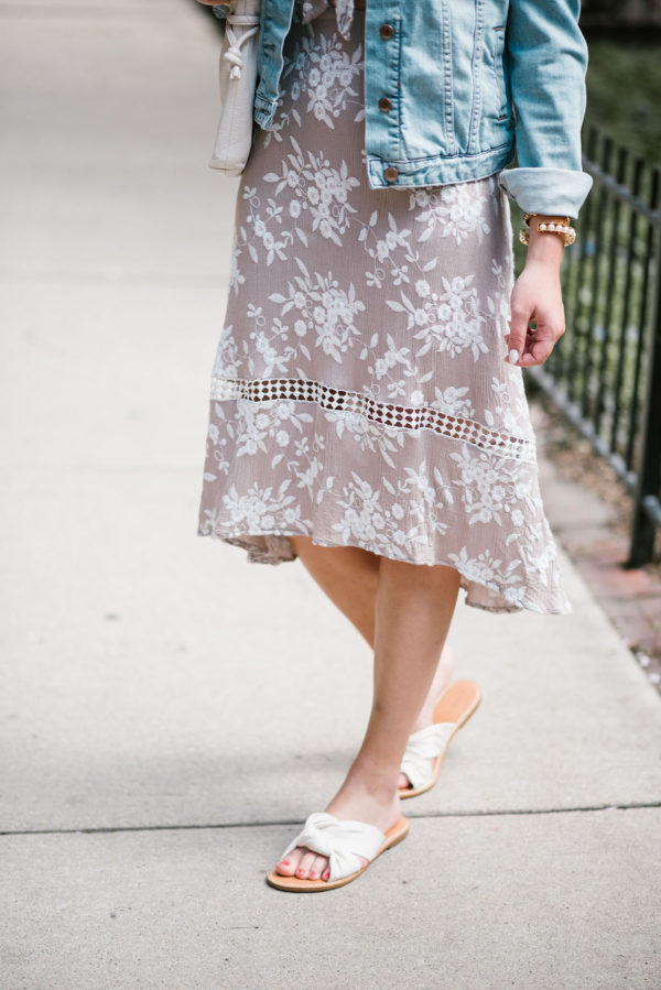Fashion stylist Bows & Sequins wearing an ASTR tie-front floral midi dress and white Soludos knotted slides with a pearl cuff.
