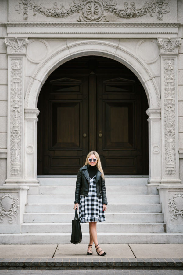 Chicago blogger Bows & Sequins wearing a Topshop moto jacket, Modcloth gingham dress, and Zara patent strappy Mary Janes with a leather tote and Nordstrom sunglasses.