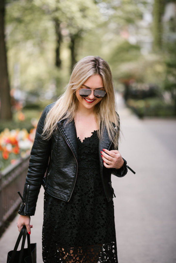 Jessica of Bows & Sequins wearing Celine mirrored aviator sunglasses, a black Topshop moto jacket, and a black lace dress.