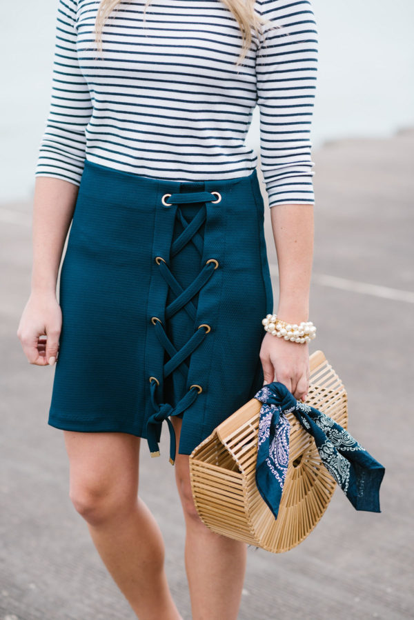 Jessica Sturdy of Bows & Sequins, a Chicago based fashion blog, wearing a Lands End striped tee and a navy skirt with a Cult Gaia bamboo bag, a navy bandana, and a Sweet & Spark pearl bracelet.