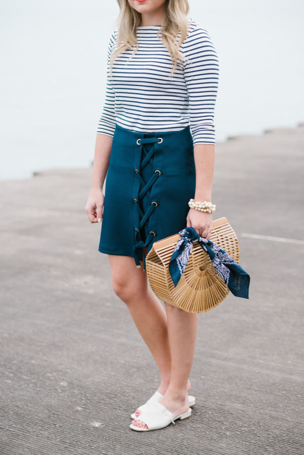 Fashion blogger Jessica Sturdy of Bows & Sequins styling a navy lace-up skirt with a striped tee, pearl bracelet, bamboo handbag, and white slides.