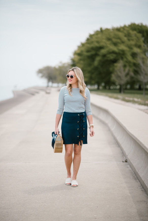 Bows & Sequins wearing a Lands End striped tee, navy lace-up skirt, and Kurt Geiger slides in Chicago.