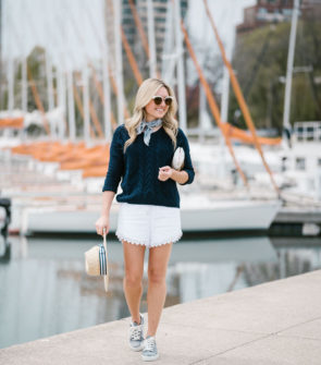 Bows & Sequins wearing a navy summer sweater and white eyelet shorts with gingham shoes, Nordstrom sunglasses, and a straw hat.