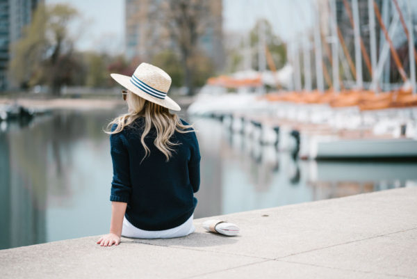Chicago blogger Jessica Sturdy wearing a Hat Attack x Lemon Stripes straw hat and a navy sweater.