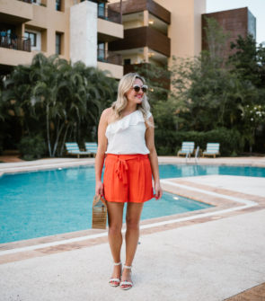 Travel writer Jessica Sturdy of Bows & Sequins wearing an Old Navy one-shoulder ruffle top with orange tie-waist shorts and J.Crew pom-pom sandals.