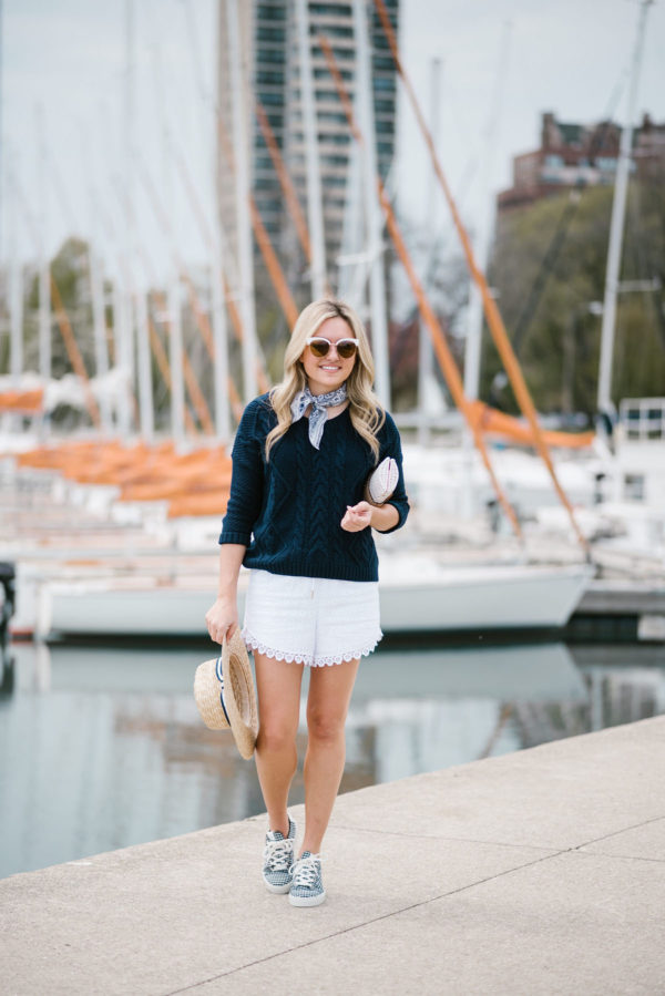 Bows & Sequins wearing a blue Echo neckerchief, a navy sweater, and white eyelet shorts with Nordstrom sunglasses and a wicker clutch.