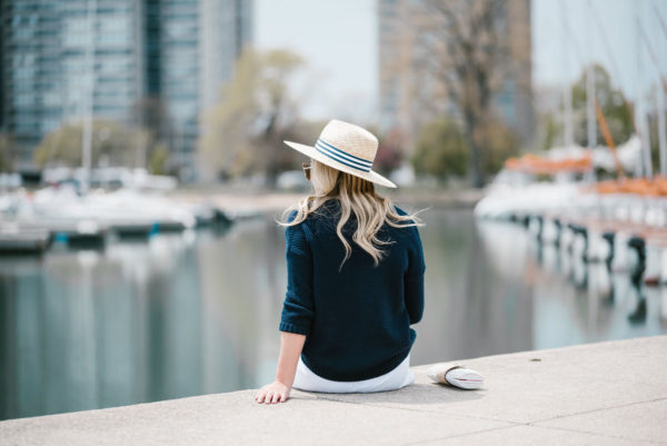 Chicago blogger Bows & Sequins wearing a straw hat with a striped band and a navy sweater.