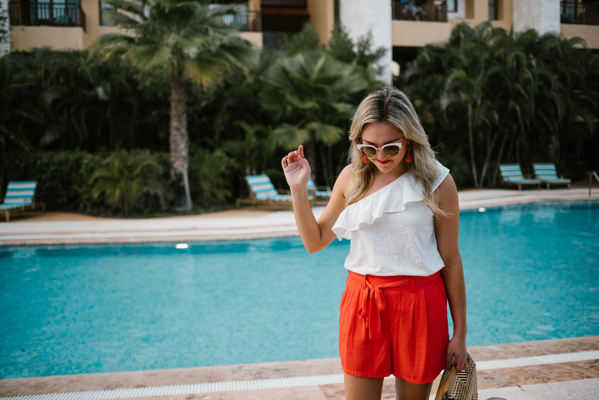 Bows & Sequins wearing a one-shoulder ruffle top with white sunglasses and orange Old Navy shorts.