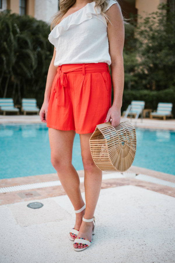 Jessica of Bows & Sequins, a Chicago based travel and lifestyle blog, wearing orange Old Navy tie-waist shorts with J.Crew pom-pom sandals and a bamboo handbag.