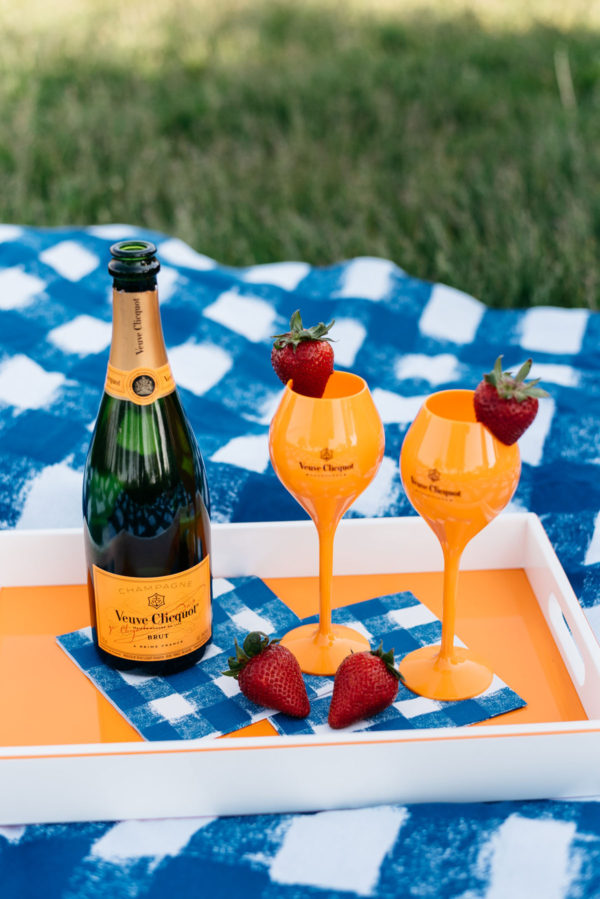 Veuve Clicquot champagne bottle and orange flutes on an orange and white lacquer tray.