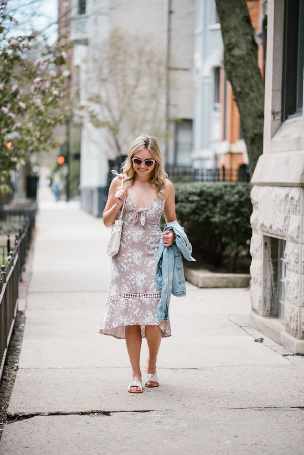 Jessica of Bows & Sequins wearing a floral tie-front dress with a Clare V Petit Henri bag, a Gap light denim jacket, white Soludos knotted slides, and Call It Spring sunglasses.
