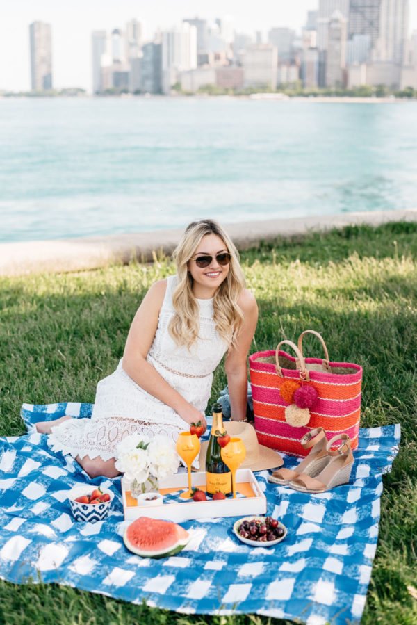 Chicago blogger Bows & Sequins wearing a white lace dress and a Mar y Sol striped tote on a gingham picnic blanket.
