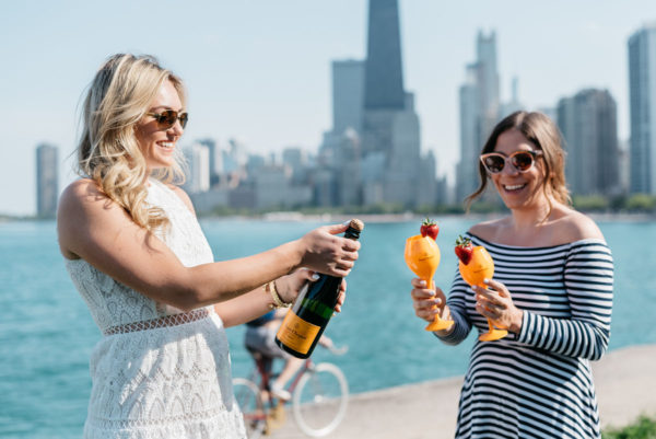 Chicago bloggers Bows & Sequins and Hallie Wilson of Among Other Things popping Veuve Clicquot champagne along Lake Michigan.