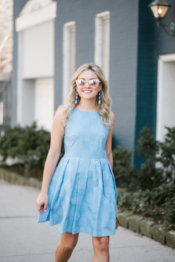 Chicago blogger Bows & Sequins wearing a blue fit and flare dress with blush pink sunglasses and blue statement earrings.