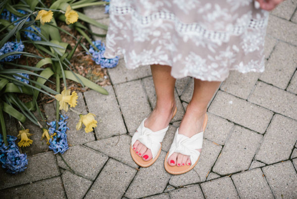Bows & Sequins wearing white Soludos knotted slides.