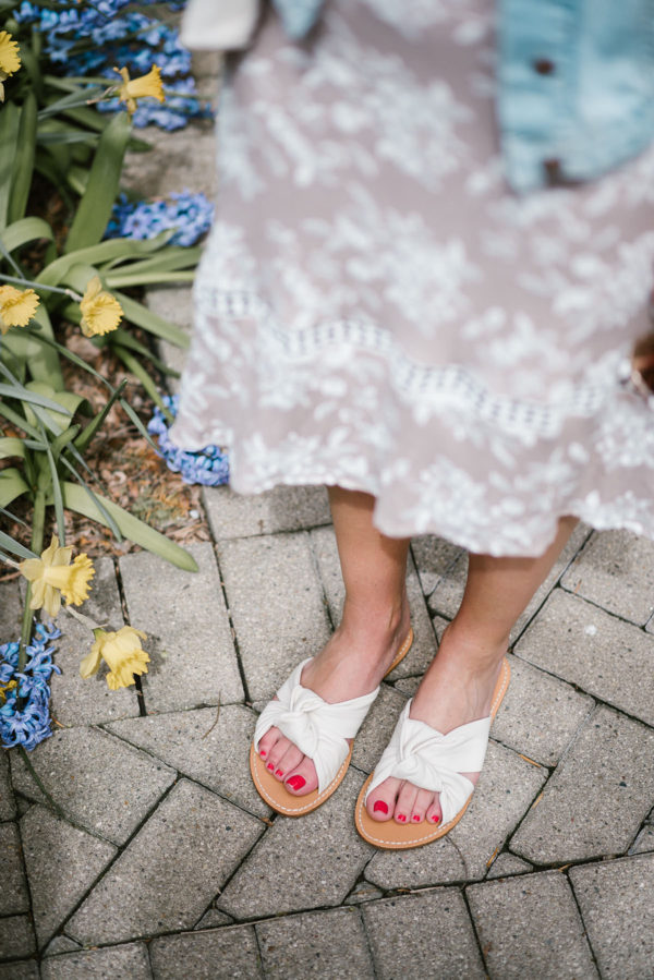 Bows & Sequins styling white Soludos knotted slides with a floral midi dress and light wash jean jacket.