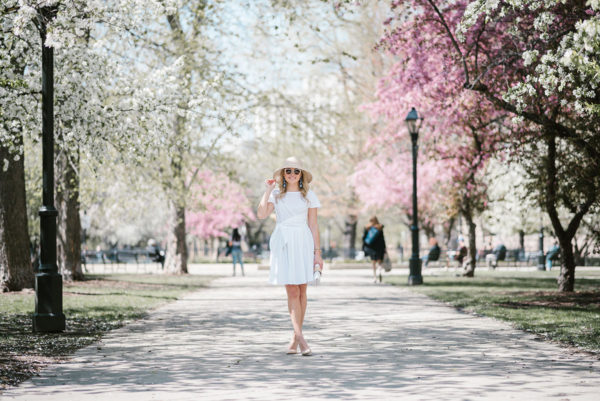 Bows & Sequins wearing a white fit and flare dress with a straw hat in Chicago during the springtime.