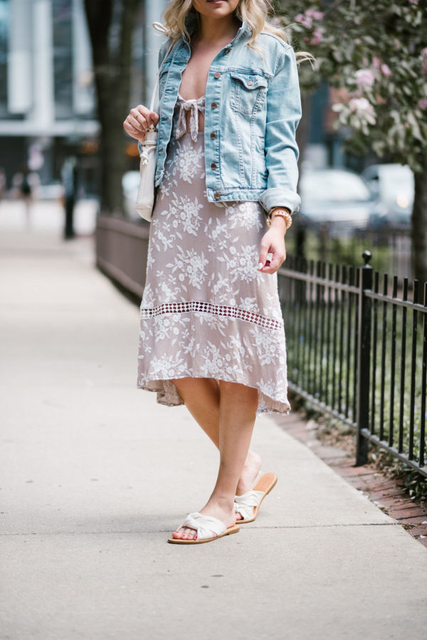 Jessica of Bows & Sequins wearing an ASTR tie-front floral midi dress with a Gap jean jacket, Soludos knotted slides, and a Clare V Petit Henri bag.