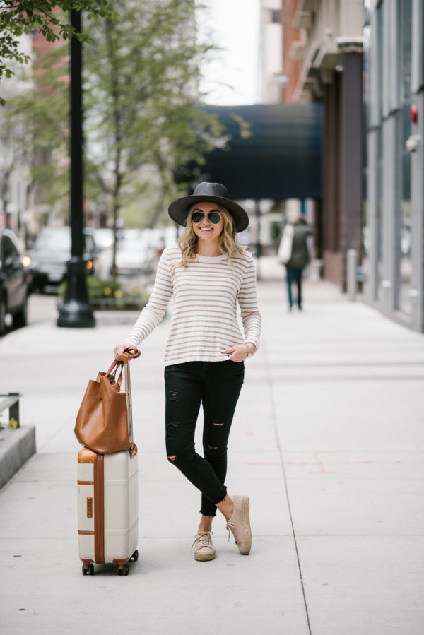 Fashion blogger Bows & Sequins wearing distressed black jeans with a striped sweater and straw hat for traveling.