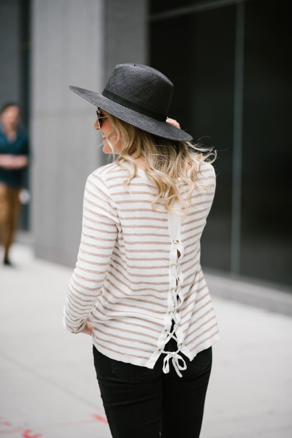 Travel writer Bows & Sequins wearing a Kenzie striped tie-back sweater with a black straw hat and Ray-Ban aviators.