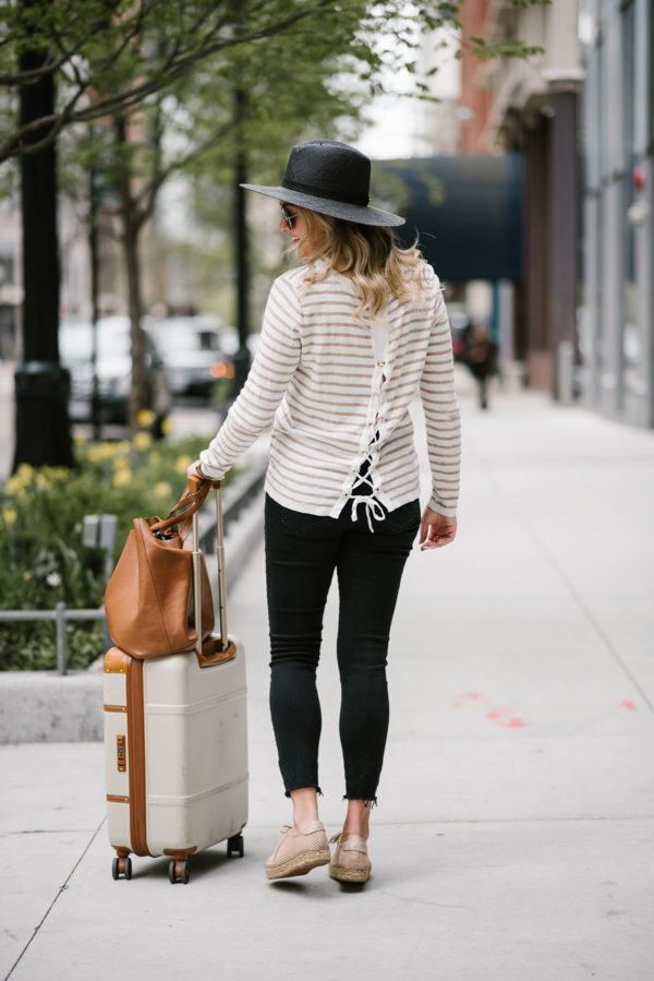 Lifestyle blogger Bows & Sequins sharing her top tips for traveling comfortably. Wearing a Kenzie tie-back sweater and Janessa Leone straw hat.