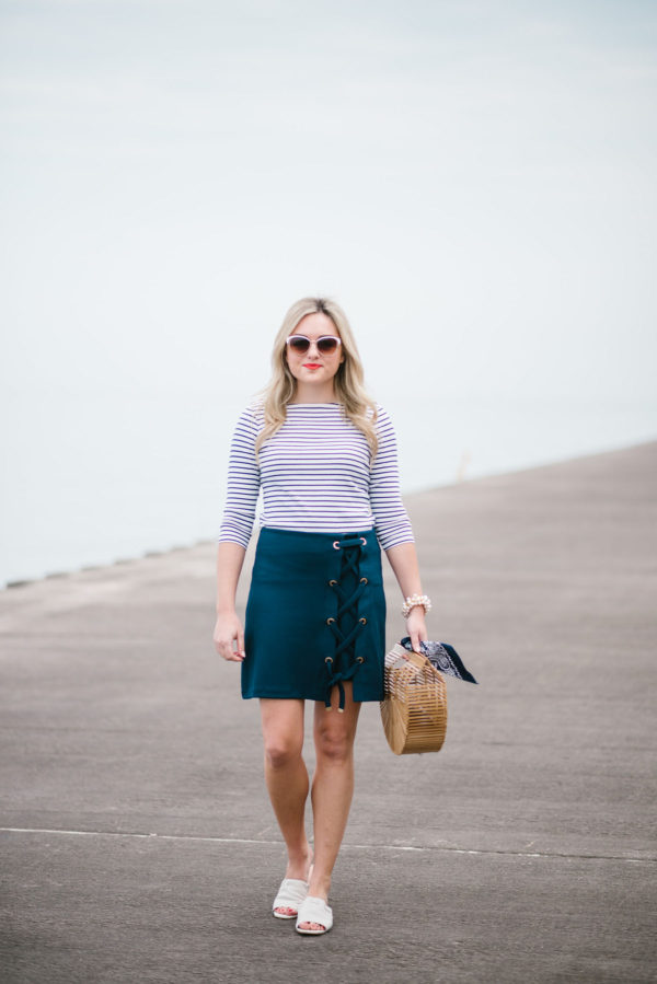 Fashion and lifestyle blogger Jessica Sturdy of Bows & Sequins wearing a lace-up skirt, striped tee, and white slides with a natural bamboo bag.