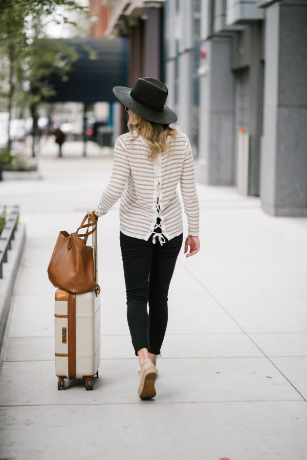 Lifestyle blogger Bows & Sequins sharing her top tips for traveling comfortably with a casual sweater, jeans, Brics bellagio suitcase and Cuyana leather tote.